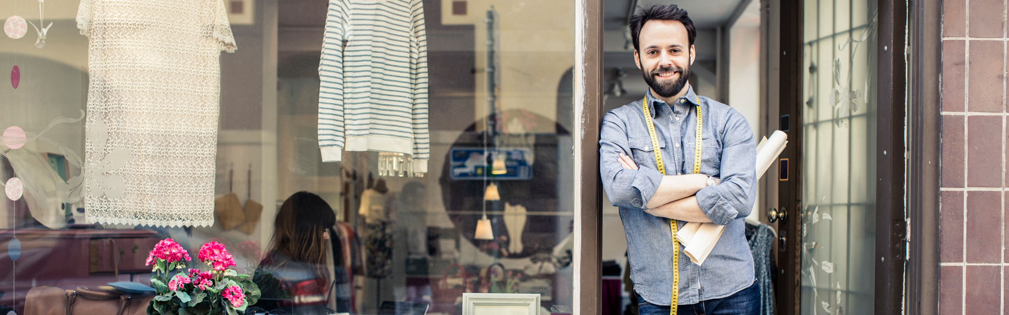Man standing in doorway of shop with clothes in window
