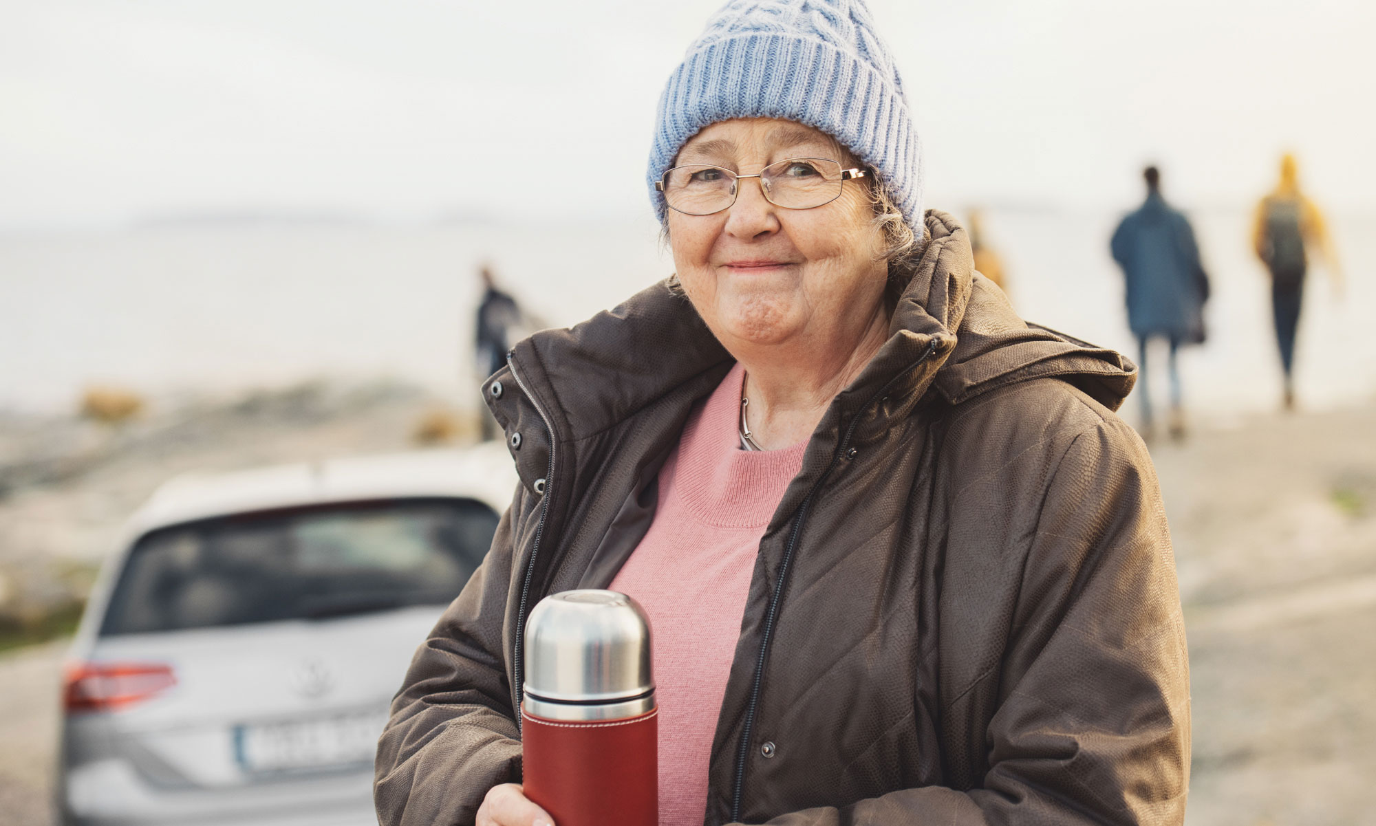 Older woman holding a thermos by the sea